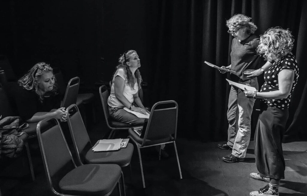 four women in the studio space reading lines and rehearsing