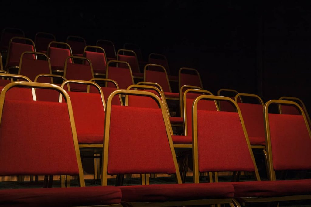 Empty raked chairs in the Theatre space at Upstairs at The Western with a spotlight on them