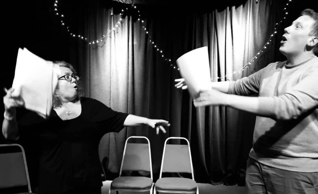 two performers with script rehearsing