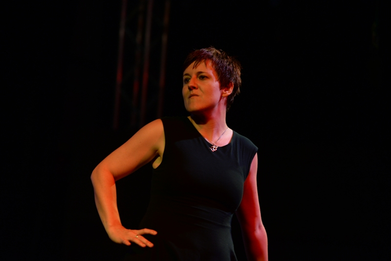 Lorna Meehan is pictured with one hand on her hip looking to her right. She is wearing black with a black backdrop behind her in stage lights.