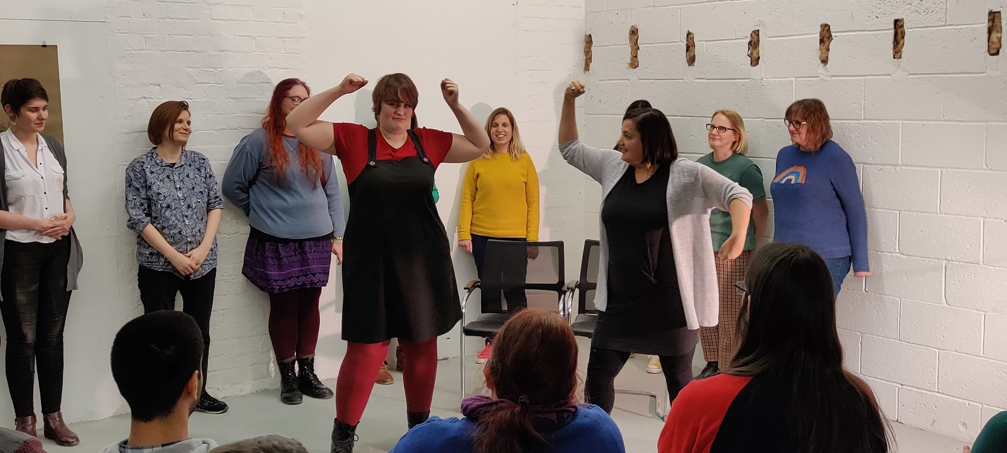A group of women are assembled against a white wall. Two women are front and centre making strong arm movements that look like one is shaking a fist and the other is shaking two fists. They look midly annoyed. The rest of the women stand against the wall watching the action unfold. There are some audience members seated in the foreground and we see the back of their heads watching the two women shaking their fists.