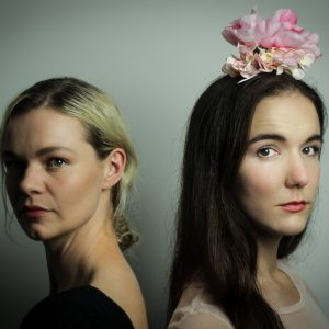 Two women face the camera with their backs to each other. There is a grey background and a dark feel to the image. Both women look haunted and one has a large pink flower on top of their head.