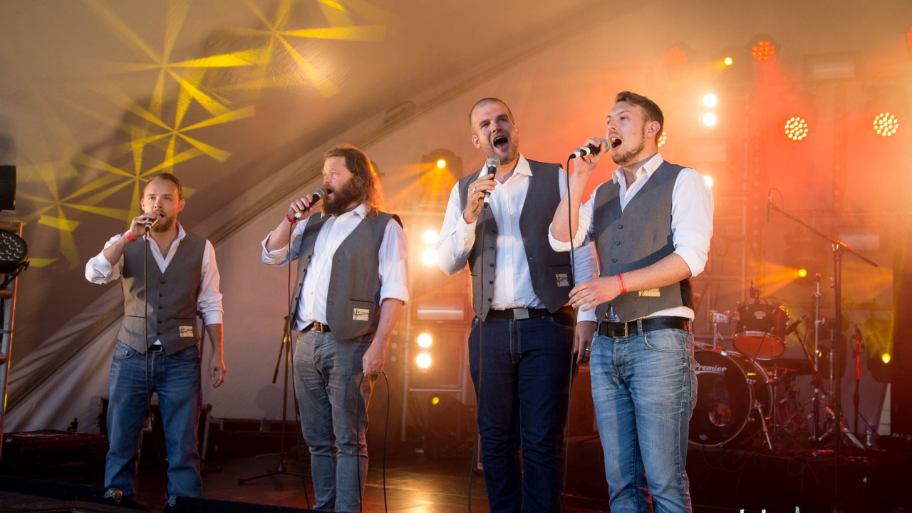 Four men are stood on a stage singing into microphones. They are all wearing jeans, shirts and waistcoats and there is yellow lights and musical equipment behind them. They look as if they are singing to an audience behind the camera.